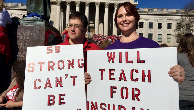 Teachers John and Kerry Guerini of Fayetteville, W.Va. hold signs at a rally at the state Capitol in Charleston, W.Va. Teachers across West Virginia will continue a walkout over pay and benefits.
