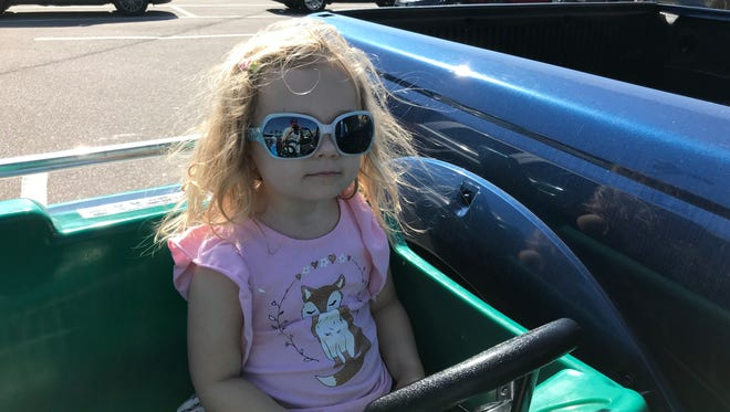 Isabella sports her new shades while riding in a space shuttle shopping cart.