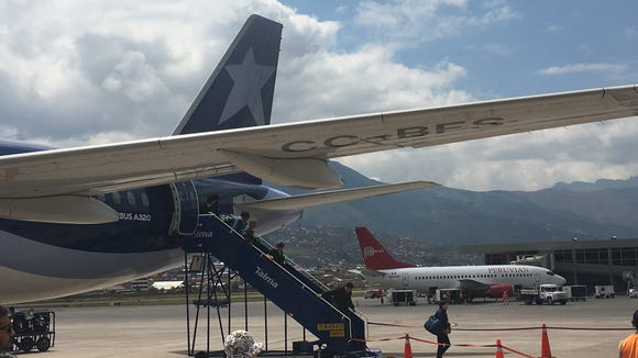 Passengers disembark a LATAM Airlines Airbus A320 -- still painted in the pre-merger colors of LAN -- upon arrival at the Alejandro Velasco Astete International Airport in Cusco, Peru, on April 19, 2018.
