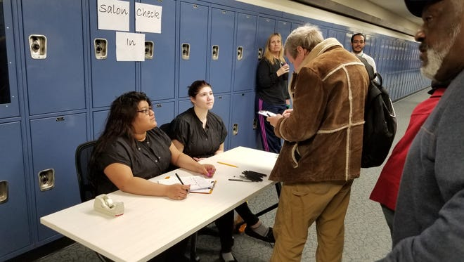 Cosmetology students Izamary Castillejos, left, a junior from New Brunswick, and Kaylee Reuter, a junior from Piscataway, register veterans for haircuts during a veterans' outreach program on April 19 on the Piscataway Campus of the Middlesex County Vocational and Technical Schools.