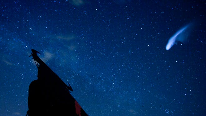 In this long-exposure photo, a streak appears in the sky during the annual Perseid meteor shower above a roadside silhouette of a Spanish fighting bull, in Villarejo de Salvanes, Spain, in the early hours of  Aug. 12, 2013.