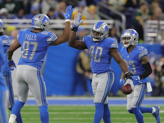 Lions' Jarrad Davis gets a high five from Darren Fells