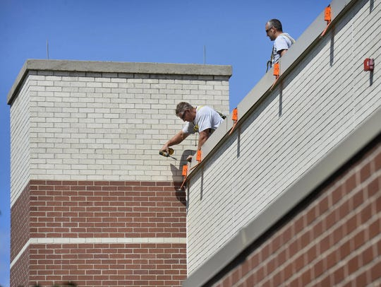 Roofers with McDowall Co., St. Cloud, set up safety