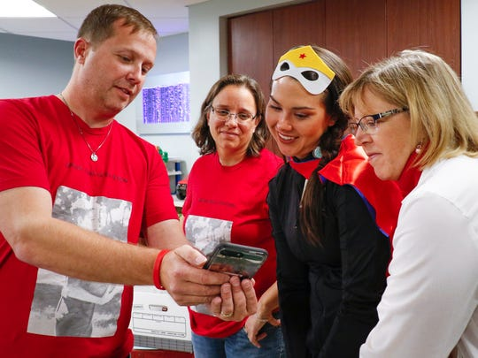 Nathan Chance of Grand Ledge and his wife Carrie show Sparrow Pediatric employees Aileen Hansen and Karen Restum, right,  a video of their late son Malachi on Tuesday, Oct. 31, 2017, at Sparrow Hospital.  The community gathered toys to donate to the Sparrow Pediatric Playroom in memory of his life.   Malachi died Oct. 31, 2016, as a result of injuries sustained in an accident five days earlier when he and his brother were hit by a car while crossing the street.