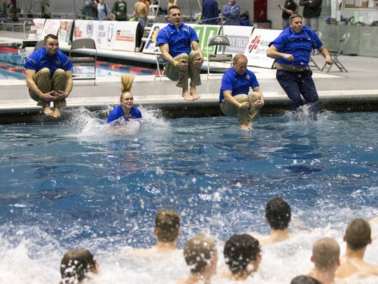Carmel High School swim coaches jump into the diving well, after their athletes took the jump, in celebration of the boys' IHSAA state title, with a new record of 417, Indianapolis, Saturday, Feb. 24, 2018.