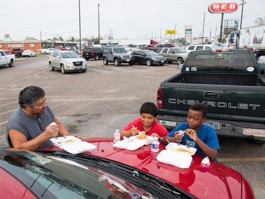 Frankie Solis, his nine-year-old son Frankie Solis Jr. and nine-year-old Zander Wills eat their meals on the hood of their car in the Refugio HEB after getting them from the HEB disaster response team on Wednesdays, Sept. 6, 2017. US Highway 77 was lined with cookers and grills as people came from all over Texas to help with hot meals in Refugio after Hurricane Harvey.