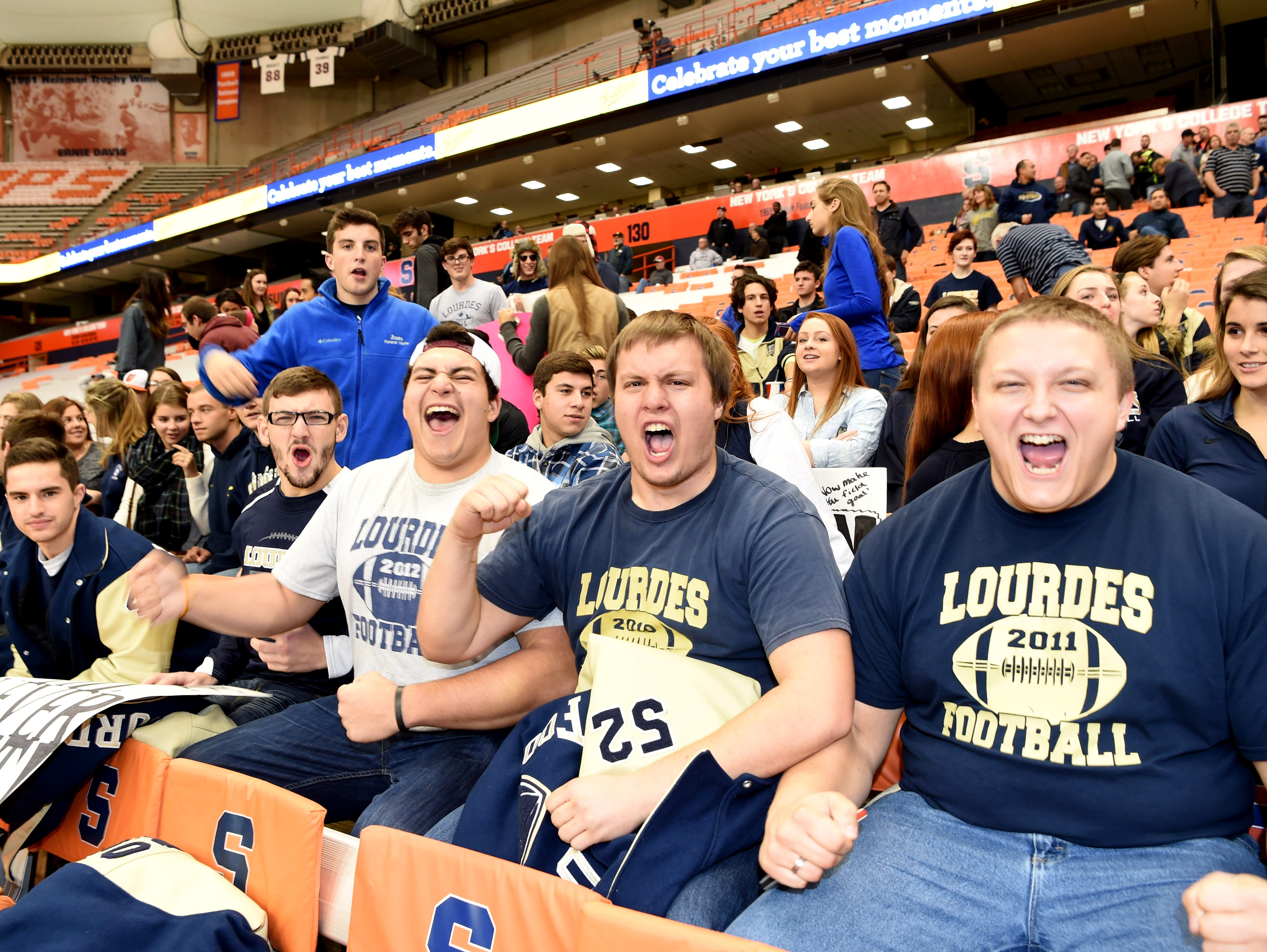 Fans from Poughkeepsie cheer on Our Lady of Lourdes football at the New York State Championships in Syracuse on Friday.