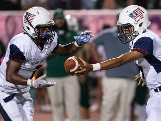 Tulare Western quarterback Elijah Burrell hands off to Rolondo Holmes in an East Yosemite League high school football game against Porterville on Friday, October 5, 2018. Both teams were 4-0 going into the game.