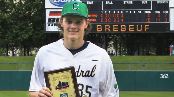 Cathedral pitcher Ashe Russell holds the City baseball tournament championship trophy after pitching a 10-0 no-hitter -- his second consecutive no-hitter to win the city tournament -- as Cathedral defeated the Trojans 10-0 at Victory Field in Indianapolis on Saturday, May 17, 2014.