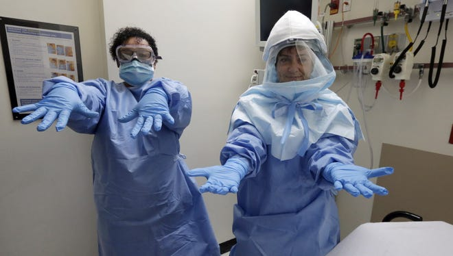 Bellevue Hospital nurse Belkys Fortune, left, and Teressa Celia, Associate Director of Infection Prevention and Control, pose in protective suits in an isolation room.