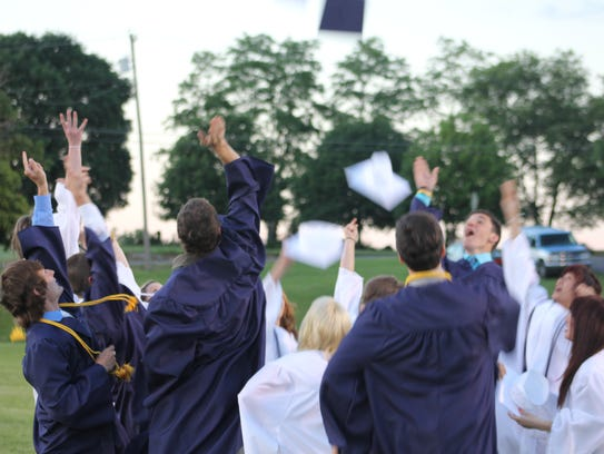 A file photo of students throwing their caps during