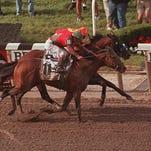 FILE - In this June 7, 1997, file photo, Touch Gold and jockey Chris McCarron, bottom, pass Silver Charm and jockey Gary Stevens, top, and Free House, left, to win the Belmont Stakes horse race at Belmont Park in Elmont, N.Y. . (AP Photo/Bill Kostroun, File)