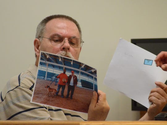 Dennis Norrod views pictures during his testimony for the defense.