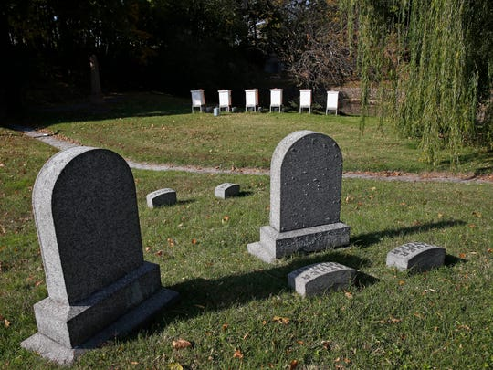 Tombstones rest on a path near six honeybee hives.
