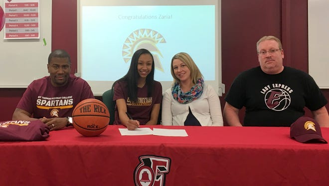 Elmira's Zaria Thomas signs a ceremonial National Letter of Intent on Tuesday at Elmira High School while seated alongside her parents, Jeremy Abrams and Sandra Abrams. On the far right is Elmira head coach Jake Dailey.