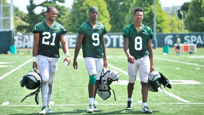 From left, wide receivers Cam Chambers, Donnie Corley and Trishton Jackson walk off the field after Michigan State football practice Wednesday.