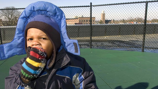 Amir Nunn, 3, chews on a chunk of ice while playing in the Crispus Attucks Early Learning Center rooftop playground.