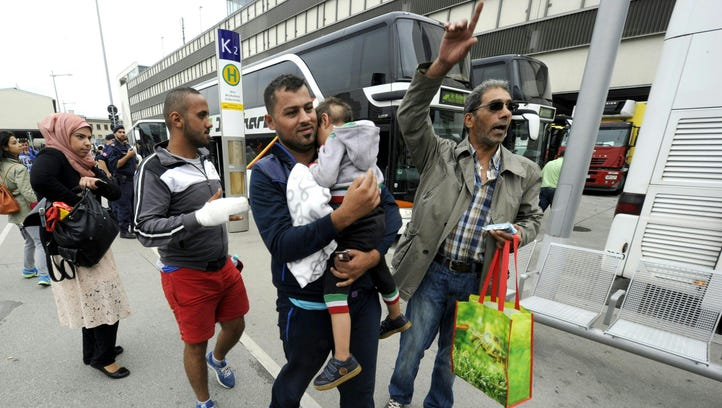 Refugees after getting off a bus arrive from the Hungarian