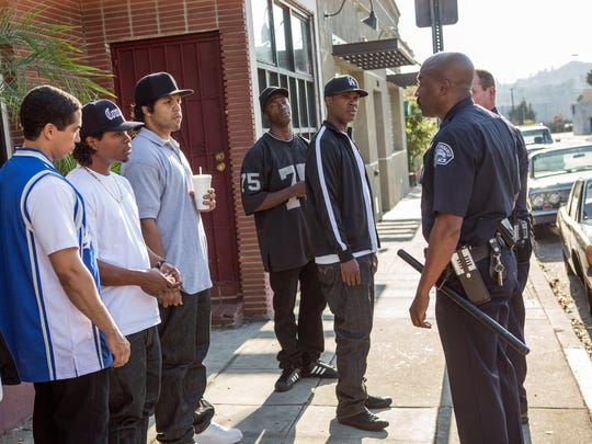 "Neil Brown, Jr., from left, as DJ Yella, Jason Mitchell as Eazy-E, O'Shea Jackson Jr. as Ice Cube, Aldis Hodge as MC Ren, and Corey Hawkins as Dr. Dre are seen with police in a scene from the film ""Straight Outta Compton."""