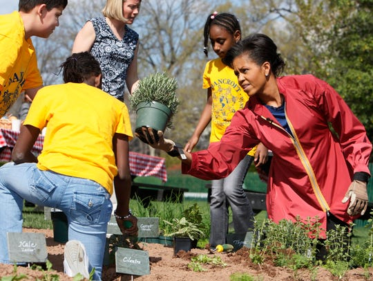 First lady Michelle Obama plants herbs on the White