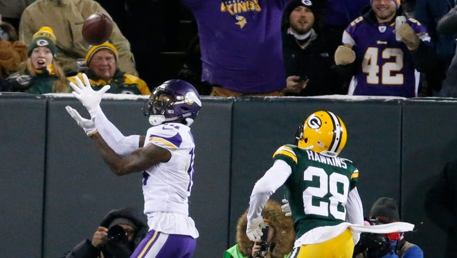 The Minnesota Vikings' Stefon Diggs catches a touchdown pass in front of the Green Bay Packers' Josh Hawkins during the first half.