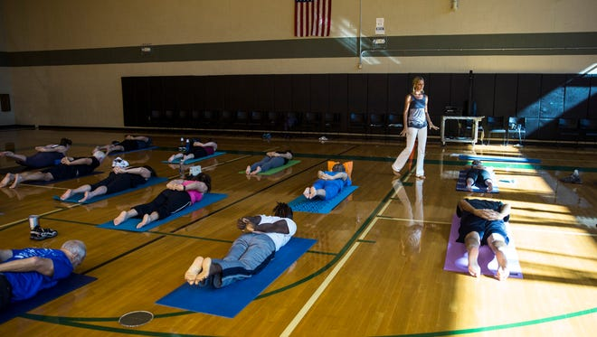 "Wendy Campbell, 41, leads a yoga class at the North Collier Regional Park gym on Friday, Dec. 16, 2016. Campbell, who was diagnosed with hodgkin's lymphona 10 years ago, is trying to bridge that gap between cancer treatment and mental well-being through her start-up organization called ""Survive & Thrive."" Campbell teaches cancer survivor yoga and provides them with other wellness resources."