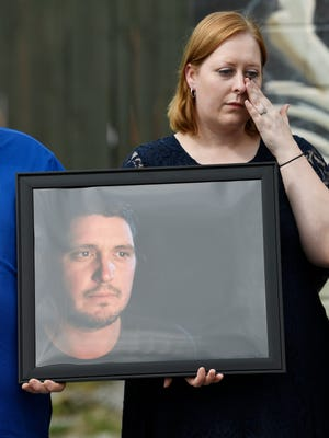 Amanda Tuttle, sister of Nashville shooting victim Bartley Brandon Teal, holds a photo of her brother at a press conference at The Cobra Tuesday, Aug. 21, 2018, in Nashville, Tenn. Teal died Friday in a shooting outside the bar.