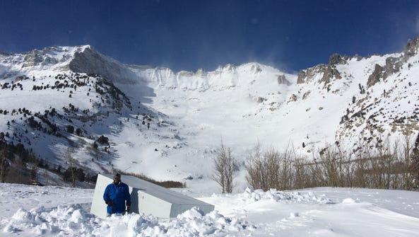Snow surveyor Logan Jenson stands in an avalanche debris