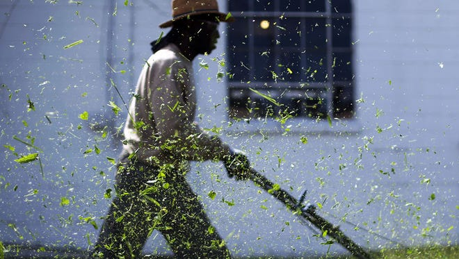 Otties Parker mows grass behind a business on Front Street in Murfreesboro.