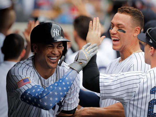 Giancarlo Stanton, left, celebrates with teammates, including Aaron Judge, rear right, after hitting a home run.