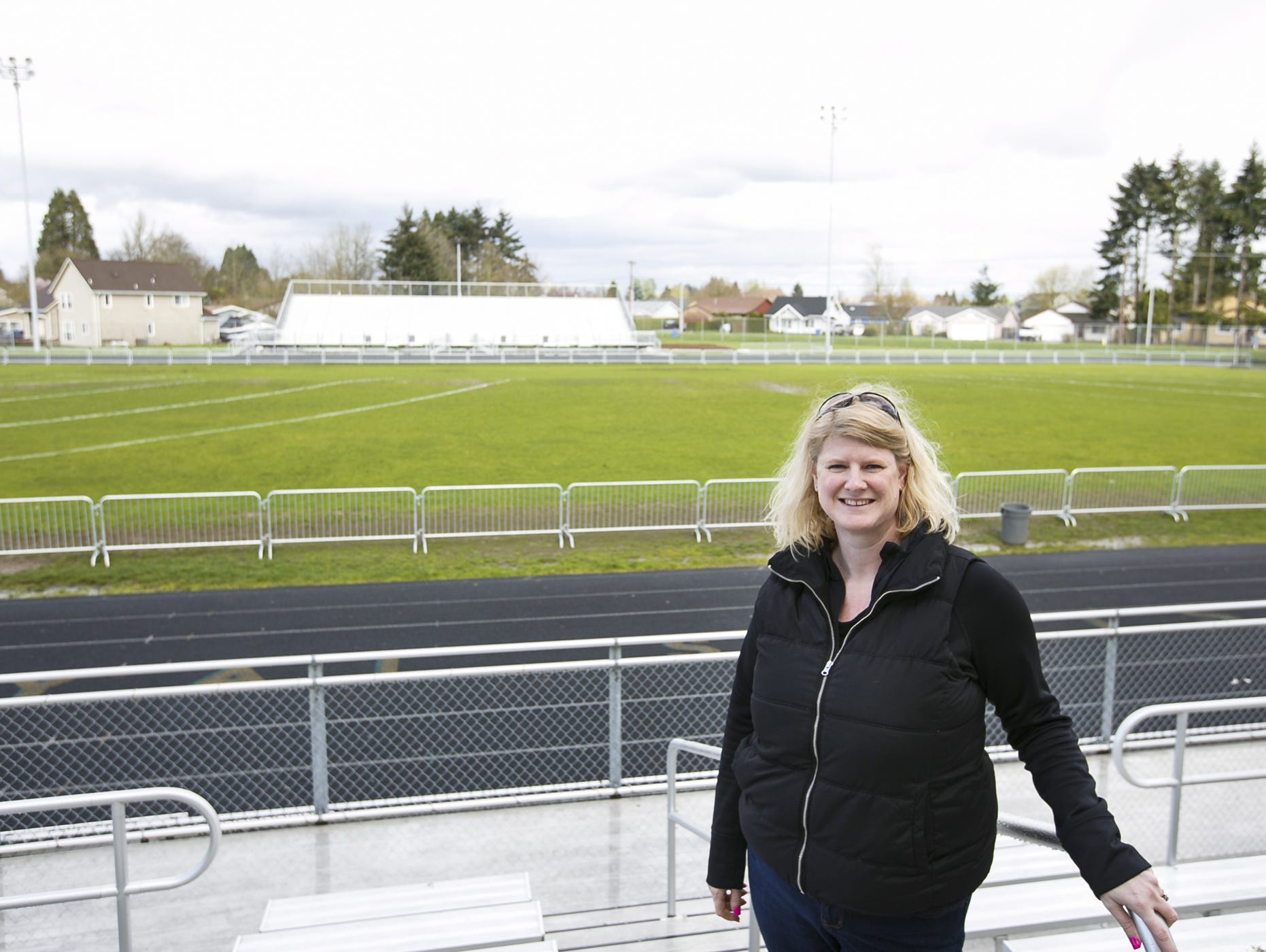 McKay booster club president Becky Bryant stands in front of McKay High School's football field on Friday, March 24, 2017. McKay is the only school in the Salem-Keizer district that still uses a grass football field, but they are schedule to have a new turf surface by this fall after a long fundraising effort.