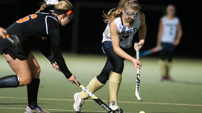 Essex's Kathleen Young (9) runs past Middlebury's Emma Snyder-White (6) with the ball during the girls semifinal field hockey game between Middlebury and Essex at Middlebury College on Wednesday.