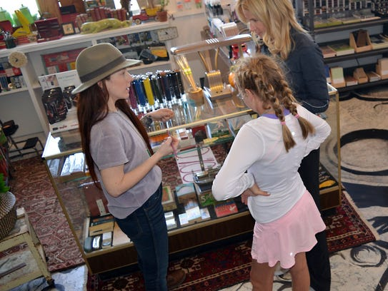 Store co-owner Nicole Wyatt Jenkins, left, assists