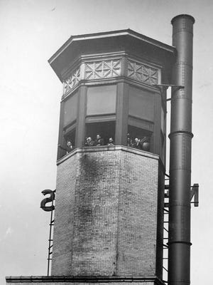 Indianapolis Fire Tower - members of the Smoke Abatement League watch from the fire tower on the Merchants Bank building.  The league kept watch on pollution production in the city. Ironically next to a smoke stack. 1929 file photo
