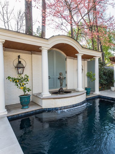The cabana is designed to mimic the look of a pool house but is actually a façade. The shutters are handmade of grandis eucalyptus wood, which is durable for outdoor use.