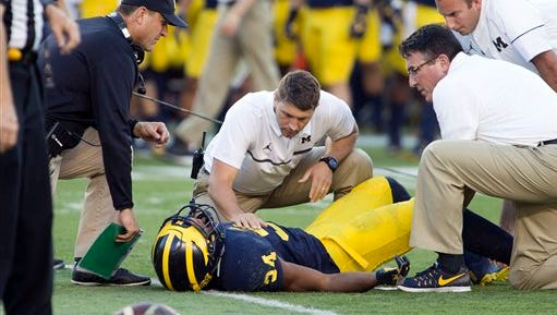 Michigan coach Jim Harbaugh, left, looks over trainers attending to cornerback Jeremy Clark on Saturday.
