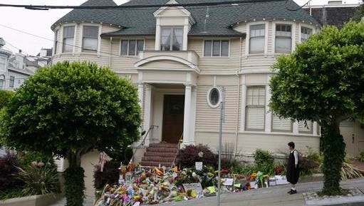"""FILE - In this Aug. 15, 2014 file photo, a woman stops to look at a makeshift memorial for actor Robin Williams outside a home which was used in the filming of the movie """"Mrs. Doubtfire"""" in San Francisco. The iconic """"Mrs. Doubtfire"""" house, which served as a temporary shrine to Williams after his suicide in 2014, has sold for $4.15 million."""