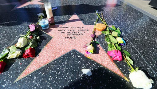 "Flowers and candles adorn an impromptu memorial created on a blank Hollywood Walk of Fame star by fans of late actress and author Carrie Fisher, who does not have an official star on the world-famous promenade, in Los Angeles Wednesday, Dec. 28, 2016. Paste-on letters spell out her name and the phrase ""May the force be with you always. Hope."""