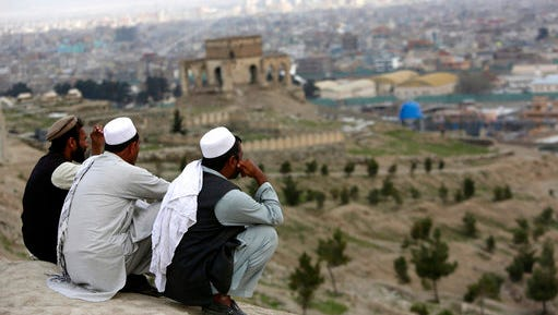 "In this March 27, 2017, file photo, men sit on the Nadir Khan hilltop overlooking Kabul, Afghanistan. As America's 16-year war in Afghanistan drags on, Russia is resurrecting its own interest in the ""graveyard of empires."" The jockeying includes engaging the Taliban and leading a new diplomatic effort to tackle Afghanistan's future, all while Washington leaves the world guessing on its strategy for ending the conflict."