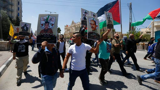 People hold posters of imprisoned during a rally in support of Palestinian prisoners in the West bank City of Bethlehem, Monday, April 17, 2017. An activist said more than 1,500 Palestinian prisoners have launched an open-ended hunger strike to demand better conditions in Israeli prisons, including more contact with relatives, and an end to Israel's practice of detentions without trial.