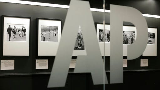 Associated Press photographs are displayed at the AP headquarters Tuesday, April 18, 2017, in New York. Earnings at the AP shrank substantially last year compared to 2015, when the news organization enjoyed a large tax benefit that skewed its results. The AP will hold its annual meeting in New York on Wednesday.