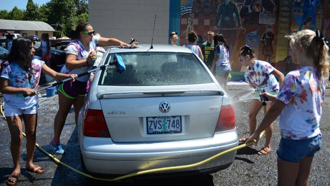 The Silverton Cheer Team washes cars to raise money for the families of Ashley Woodford and Brittany Perry Thursday, July 17, 2004. The Silverton teens were in a car accident on Sunday, July 13. Woodford was hospitalized while Perry died from injuries sustained in the crash