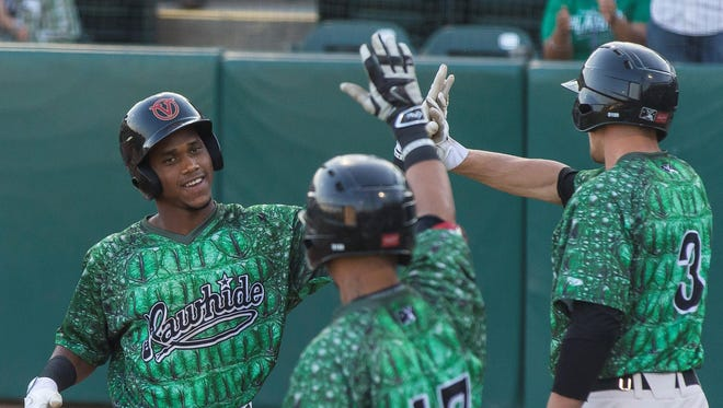 Fernery Ozuna, far left, and the Visalia Rawhide celebrate after scoring a run against the Bakersfield Blaze on Sunday in Game 2 of the California League North Division Championship series at Recreation Park.