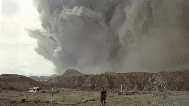 A soldier walks towards an abandoned house as Mount Pinatubo spews ash as high as 12 miles during its eruption on June 19, 1991. When Pinatubo erupted, it cooled the Earth for about a year because the sulfate particles in the upper atmosphere reflected some sunlight. Several scientists have proposed doing the same artificially to offset global warming.