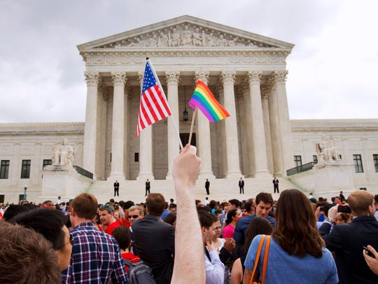 FILE - In this June 26, 2015 file photo, the crowd celebrates outside of the Supreme Court in Washington after the court declared that same-sex couples have a right to marry anywhere in the U.S. A brief exchange during Supreme Court arguments in the same-sex marriage case has exploded into a full-blown crisis for some conservatives who warn that the IRS could start revoking the tax-exempt status of religious groups that oppose gay marriage. The attorneys general of 15 states have written Congress asking for legislation to protect religious schools and other groups. Bills in the House and Senate are gaining support.(AP Photo/Jacquelyn Martin, File)