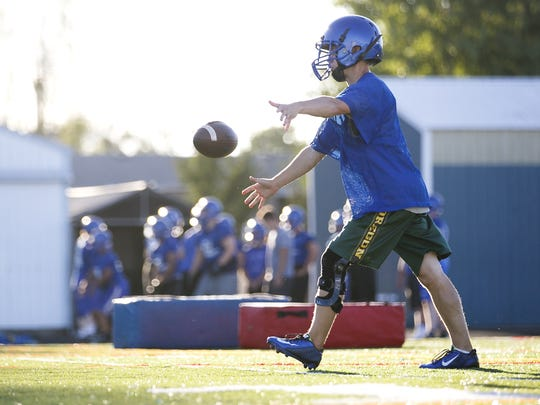 McNary High School senior A.J. Johnk warms up at a team practice on Monday, Aug. 15, 2016. After recovering from a torn ACL in 2014, Johnk is back and ready to play for the varsity team again.