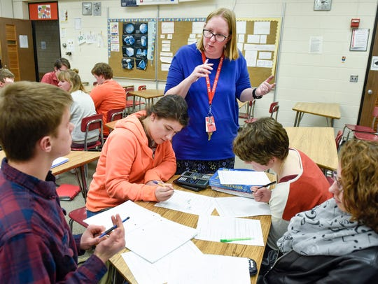 Math teacher Jean Michael works with students during