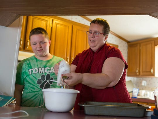 Cheryl Castle, right, makes a cake with her son Nate
