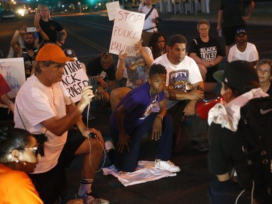 Kavi Bell, 14 (in purple) kneels with other protesters during a march against police brutality in downtown Mesa on June 8, 2018.