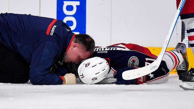 A trainer checks on Columbus Blue Jackets left wing Nick Foligno after he was injured during the third period against the Los Angeles Kings on Sunday. Foligno was taken off the ice on a stretcher.